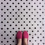 Pink shoes and black and white tile. Girl wearing pink canvas shoes standing on antique black and white tile Stock Photos