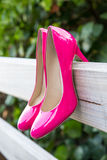 Pink shoes on fence royalty free stock image