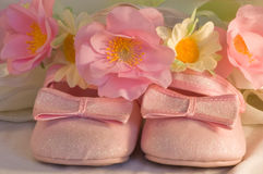 Pink shoes for a little baby. Children's pink shoes with the bows and the wreath from colours close up Stock Photo