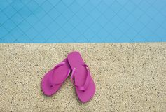 Pink shoes near blue water of swimming pool Royalty Free Stock Photography