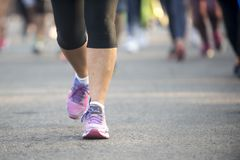 Street leg runner. Pink shoes tennis of a marathon runner during a street event stock image