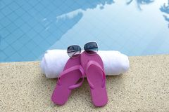 Pink shoes white towel sunglasses pool blue water Stock Image