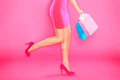 Pink shopping. Woman shopper legs, high heels and shopping bags on pink background Royalty Free Stock Images