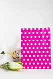 Pink shopping bag with bouquet of white lilies on white backgrou Stock Photo