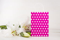 Pink shopping bag with bouquet of white lilies on white backgrou Stock Image