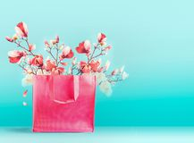 Pink shopping bag with spring blossom branches standing at turquoise blue background. Trendy color. Creative spring time and. Summer concept. Copy space for stock photos