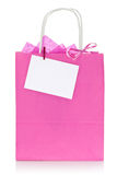 Pink shopping bag with tag. Decorative pink shopping bag with blank tag or label, isolated on white background Royalty Free Stock Photos