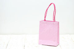 Pink Shopping bag on a wooden Stock Images