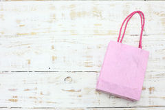 Pink Shopping bag on a wooden Stock Image