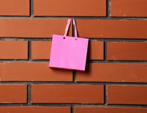 Pink shopping bags on brick wall background. Textured brick wall background with little cute pink shopping bag hang on it, copy space Royalty Free Stock Photography