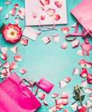 Pink Shopping bags , flowers and blank tags on turquoise background, top view royalty free stock photos