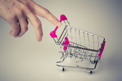 Pink shopping cart in woman hand Royalty Free Stock Photos