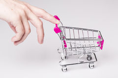 Pink shopping cart in woman hand Royalty Free Stock Images