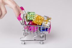 Pink shopping cart in woman hand and blue gift Stock Photo