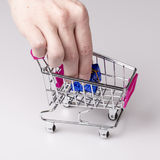 Pink shopping cart in woman hand and blue gift Royalty Free Stock Image