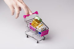 Pink shopping cart in woman hand and blue gift Stock Images