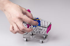 Pink shopping cart in woman hand and blue gift Stock Photography