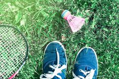 A pink shuttlecock and a badminton racket lie on the green lawn grass. At the player& x27;s feet in blue sports shoes royalty free stock photos
