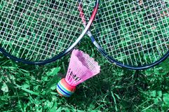 A pink shuttlecock and a badminton racket lie on the green lawn grass. At the player& x27;s feet in blue sports shoes stock photography