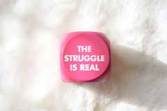 Pink sign with white lettering that says the struggle is real. Pink button with white lettering that says The Struggle is Real on white background Royalty Free Stock Photos