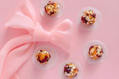 Pink silk bowknot and five healthy energy balls lying in circle on pink background. Large pink silk bowknot and five healthy energy balls made from pieces of royalty free stock photography