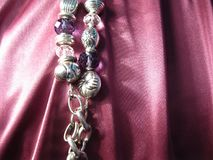 Texture of pink silk with a metal chain element and crystal beads. On pink silk with drape, an element of a metal chain Stock Image
