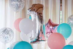 Pink, silver and blue inflatable balloons on ribbons - number 1. Decorations for birthday party. Metallic design balloon. Pink, silver and blue inflatable royalty free stock images