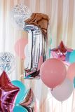Pink, silver and blue inflatable balloons on ribbons - number 1. Decorations for birthday party. Metallic design balloon. Pink, silver and blue inflatable royalty free stock photos