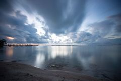 Pink and silver clouds reflecting on the ocean Stock Images
