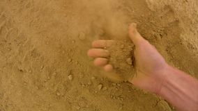 Pink skin hand looking for something in extremely dry dusty clay. Gentle wind takes away dust from palm, dust between fingers stock video footage
