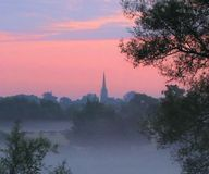 Pink skyline with church Oxfordshire countryside. Landscape view with pink sky mist and church . taken early morning over oxfordshire countryside Stock Photography