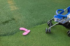 Pink slipper and part of baby stroller on green grass Stock Photography