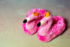 Pink Slippers with flamingo design. Fluffy pink trendy slippers with flamingo design stock photography