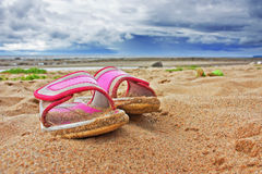 Pink slippers on sandy beach Royalty Free Stock Photography