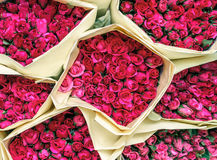 Pink small roses in paper bouquets, top view, at Bangkok flower market Thailand. Beautiful pink small roses in paper bouquets, top view, at Bangkok flower market Royalty Free Stock Photos