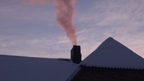 Pink smoke coming from house chimney. Pink smoke coming from private house chimney in urban area on winter's evening stock footage