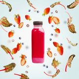 Pink smoothie bottle with flying berries and chard leaves on light blue background. Healthy detox beverages. Dieting, clean eating, vegetarian, vegan, fitness royalty free stock images
