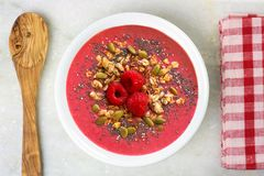 Pink smoothie bowl with superfoods, spoon and cloth Royalty Free Stock Image