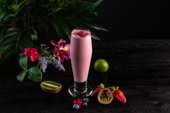 Pink smoothie in a tall glass and fruits on a dark background stock image