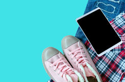 Pink sneaker, scott shirt, torn jean, smart-phone isolated on bl Stock Photos