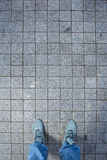 Pink sneakers from an aerial view on grey brick pavement texture Royalty Free Stock Photography