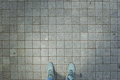 Pink sneakers from an aerial view on grey brick pavement texture Royalty Free Stock Images