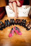 Pink sneakers among black high heeled shoes at wardrobe. Closeup photo of pink sneakers among black high heeled shoes at wardrobe Stock Photos