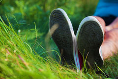 Pink sneakers on girl legs on grass Stock Images
