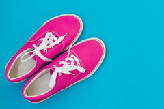 Pink sneakers with laces on a blue. Background Stock Photos