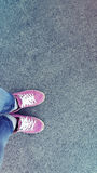 Pink sneakers shoes walking on concrete top view with sunlight. Leather shoes and feet on concrete top view background. Royalty Free Stock Photos