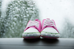 Pink sneakers toddler shoes on the car's dashboard. Pair pink sneakers toddler shoes on the car's dashboard royalty free stock photography
