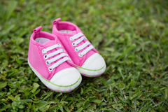 Pink sneakers toddler shoes on the grass yard, nature background. A portrait of a pair pink sneakers toddler shoes on the grass yard, nature background concept royalty free stock photos