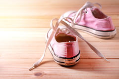 Pink sneakers on wooden floor Royalty Free Stock Photography
