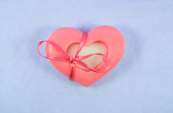 Pink soap in the shape of a heart with a ribbon on tulle Stock Image